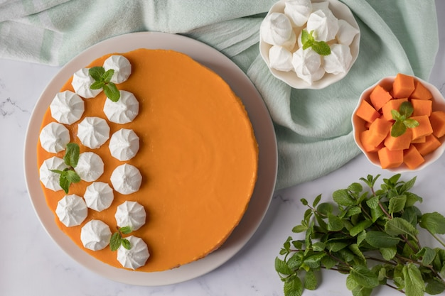 Composition with tasty pumpkin cheesecake on marble table, flat lay