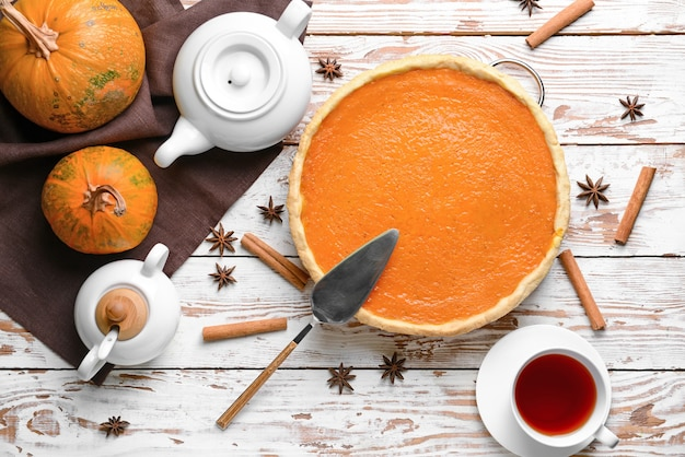 Composition with tasty pumpkin pie and tea on wooden table