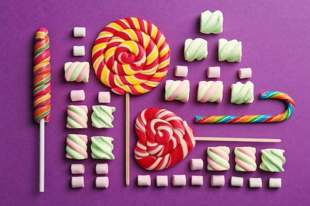 Composition with tasty sweets on purple, top view