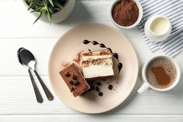 Композиция с вкусным тирамису и какао напиток на белый деревянный стол. вкусный десерт