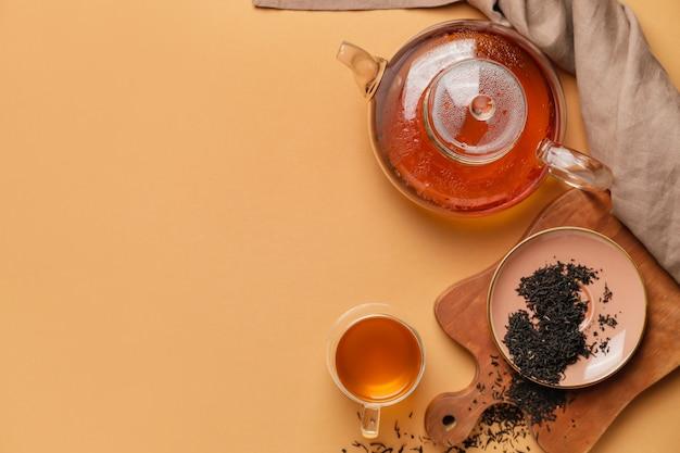 Композиция с чайником и чашкой чая на апельсине, вид сверху