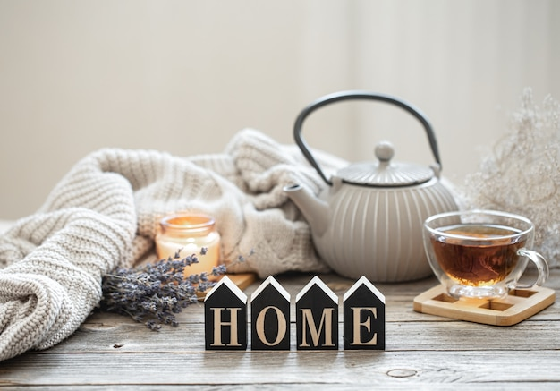 Composition with teapot and tea on a wooden surface with a knitted element, cozy details and the decorative word home