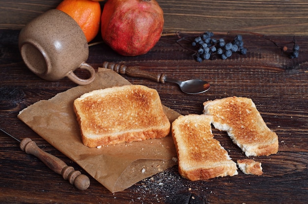 Composition with toasted bread and different objects on old wooden table