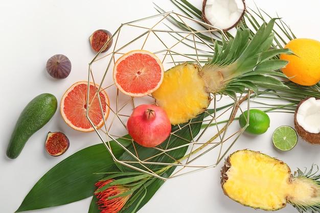 明るい背景に熱帯の葉とエキゾチックなフルーツとの構成