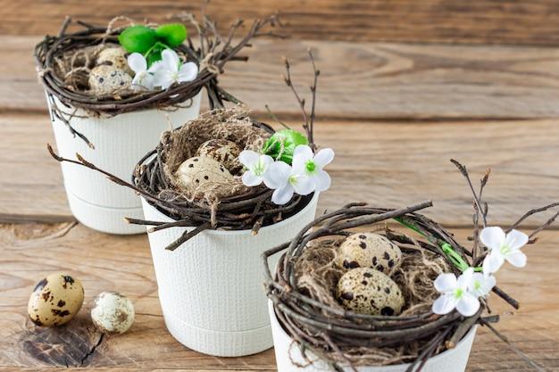 냄비에 나뭇가지 둥지와 메추라기 알이 있는 구성. 소박한 스타일의 부활절 휴일입니다.