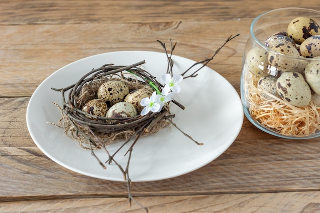 접시에 나뭇가지 둥지와 메추라기 알이 있는 구성. 소박한 스타일의 부활절 휴일입니다.