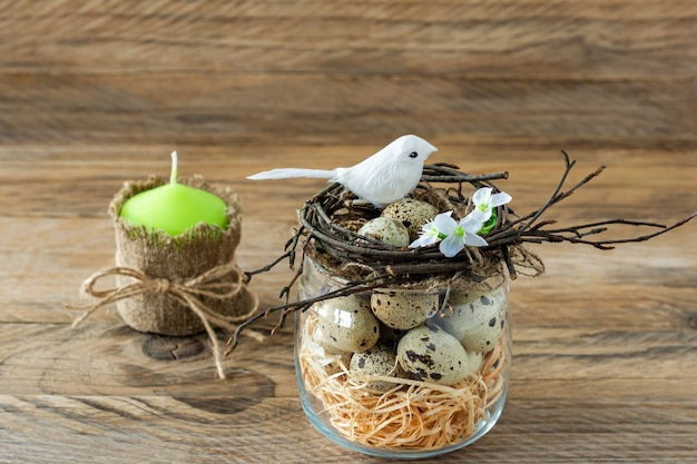 나뭇가지 둥지, 메추라기 알, 작은 새들로 구성된 구성. 소박한 스타일의 부활절 휴일입니다.