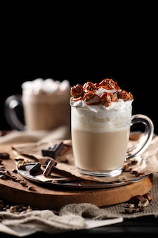 Composition with two glass of cappuccino topped with whipped cream and served