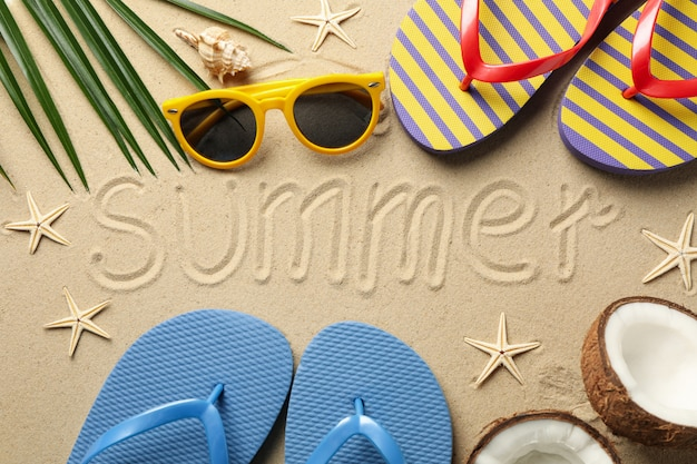 Composition with vacation accessories and inscription summer on sea sand surface