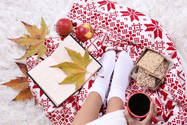 따뜻한 격자 무늬 책 컵과 컬러 카펫 배경에 여성 다리가 있는 구성