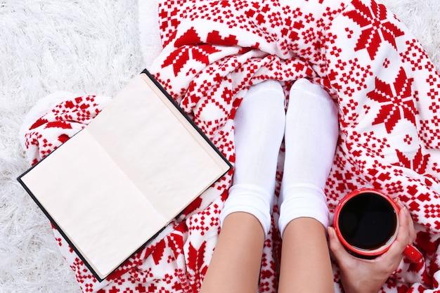 컬러 카펫 배경에 따뜻한 격자 무늬, 책, 뜨거운 음료 및 여성 다리가 있는 구성