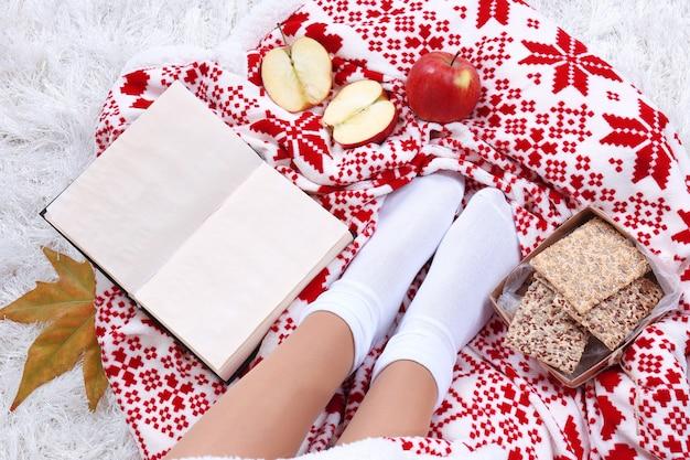 カラーカーペットの背景に、暖かい格子縞、本、温かい飲み物と女性の足のカップで構成