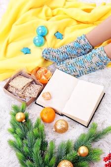 컬러 카펫 배경에 따뜻한 격자 무늬, 책, k 및 여성 다리가 있는 구성