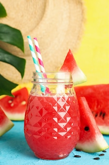 Composition with watermelon juice on blue table. summer fruit