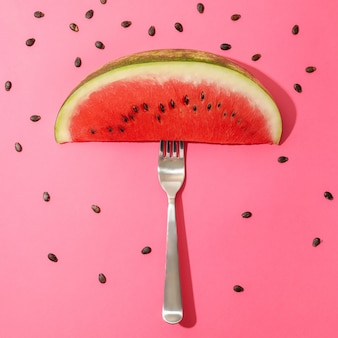 Composition with watermelon slice, fork and seeds on pink