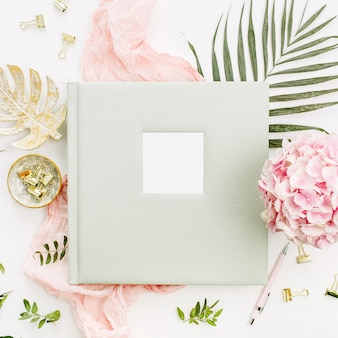 結婚式や家族の写真アルバム、アジサイの花の花束、熱帯のヤシの葉、パステルピンクの毛布、白い表面にゴールドのモンステラプレートとの構成