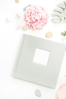 結婚式や家族の写真アルバム、ピンクのアジサイの花の花束、白い表面にモンスターの葉のプレートとの構成