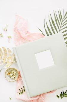 結婚式や家族の写真アルバム、熱帯のヤシの葉、パステルピンクの毛布、白い表面にゴールドのモンステラプレートとの構成