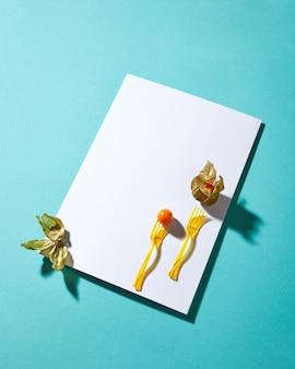 白い空白のカードと黄色のサイサリス植物とハードシャドウと青い背景のフォークで構成。テキスト用のスペース。モダンなスタイル。