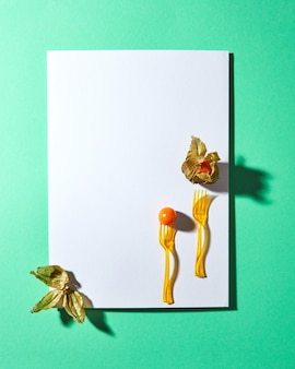 白い空白のカードと黄色のサイサリス植物とハードシャドウと緑の背景にフォークで構成。テキスト用のスペース。モダンなスタイル。