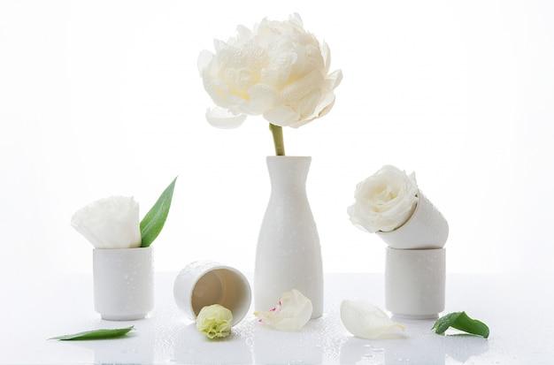 Композиция с белыми цветами и каплями воды на белой стене, натюрморт из роз, копией пространства