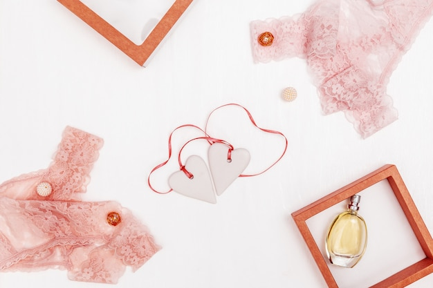 Composition with  white hearts together with pink ribbon, women lace lingerie, perfume on white holiday concept for wedding, valentines day, romantic relation.