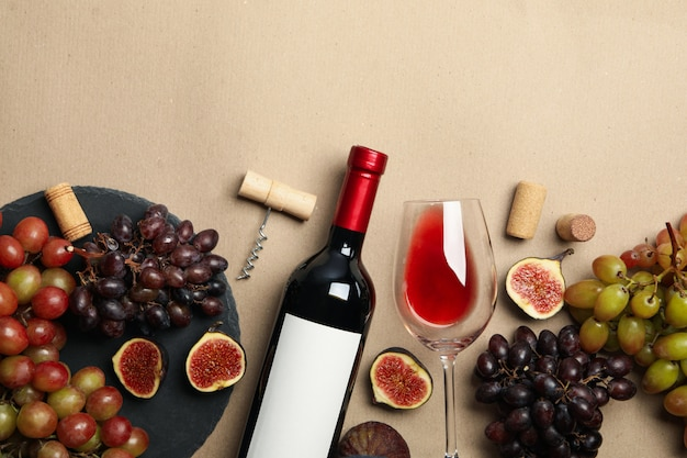 Composition with wine and fruits on craft background, space for text