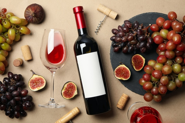 Composition with wine and fruits on craft background, top view