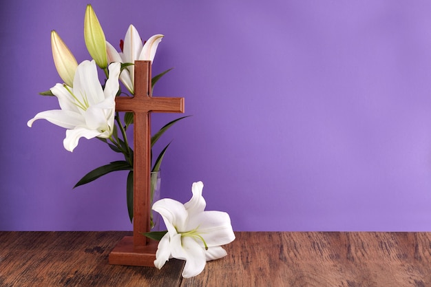 Composition with wooden cross and lily on purple background