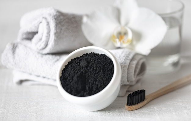 Состав с деревянной натуральной зубной щеткой и черным порошком для отбеливания зубов.