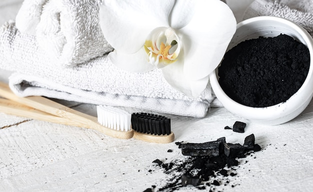 Composition with a wooden natural toothbrushes, black teeth whitening powder and orchid flower copy space.