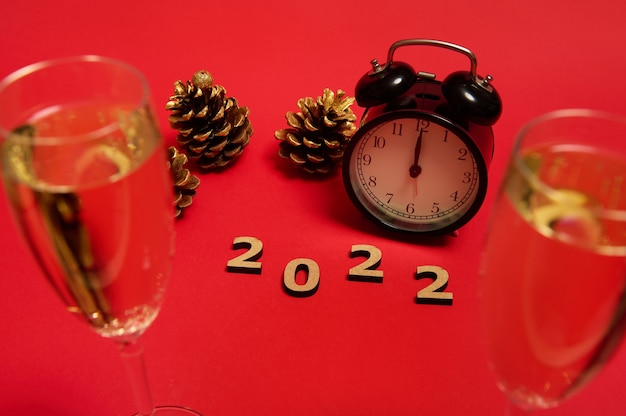 Composition with wooden numerals, 2022 year, black alarm clock with midnight on the clock face, golden pine cones and champagne flutes with a sparkling wine on a red background with copy space for ad