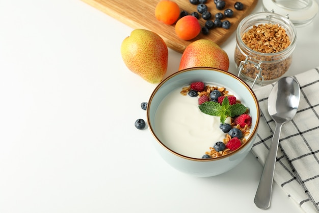Composition with yogurt dessert and ingredients on white background,