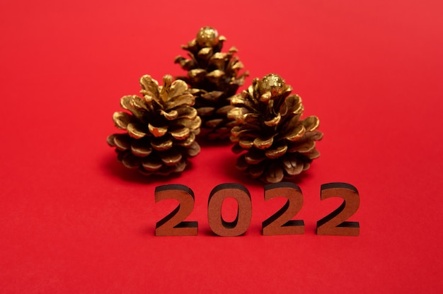 Composition of wooden numerals symbolizing the year 2022 on the red background with pine cones with golden decorations. studio shot of christmas and new year objects with copy space for ad
