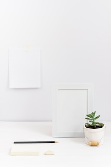 Composition of workplace with white frame and plant vase