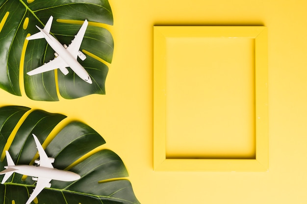 Composition of yellow board monstera leaves and small white airplanes