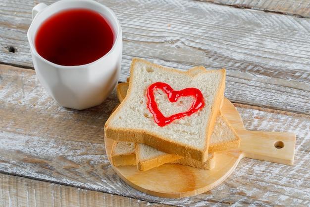 Composta in una tazza con inceppamento sulla vista dell'angolo alto del pane del pane tostato sul tagliere di legno e