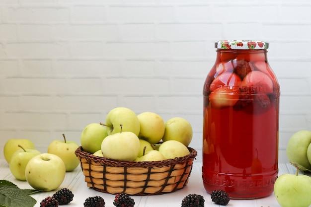 白い背景の上のテーブル、そこにリンゴ、ブラックベリーの瓶の中のベリーとリンゴのコンポート。碑文のための無料の場所