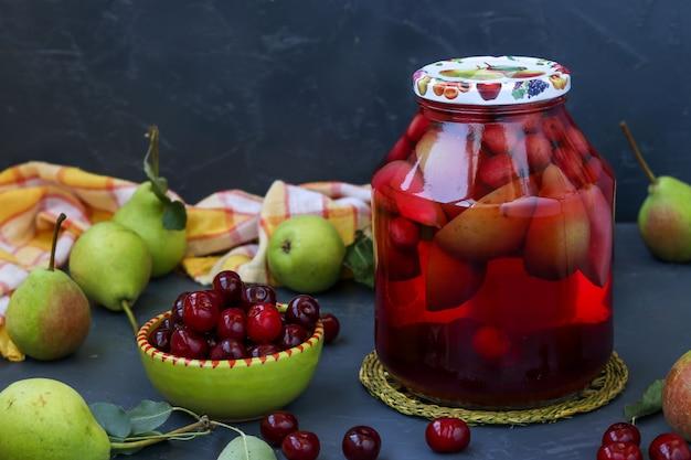 暗い背景に瓶に梨とチェリーのコンポート、冬の収穫、水平方向、クローズアップ