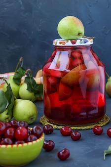暗い表面に瓶に梨とチェリーのコンポート、冬の収穫、垂直写真