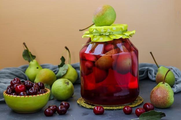 テーブルの上の瓶の中の梨とサクランボのコンポート、冬の収穫、水平方向、クローズアップ