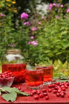 Компот с кизилом в двух прозрачных стаканах и банке на красном деревянном столе