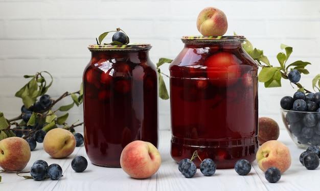 缶詰のブラックソーンの桃とベリーのコンポートは、白い背景にあります