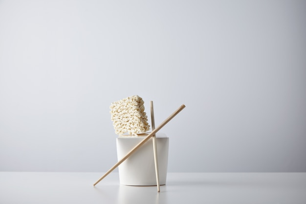 Compressed dry noodles brick presented on top of blank takeaway box with chopsticks isolated on white in center