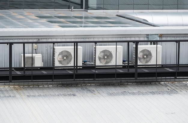 The compressor unit row of the air conditioner system on the top of the modern commercial building,  working all day in the summer, front view with the copy space.