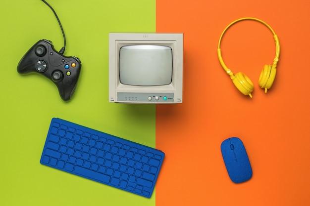 オレンジグリーンの背景にコンピュータアクセサリとゲーム機。ゲームと教育の技術。フラットレイ。