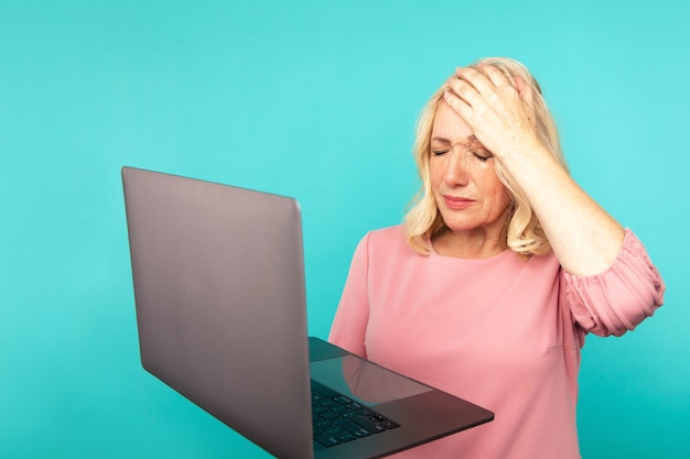 Computer bad news. frustrated upset woman holding laptop and do not knpw what to do.