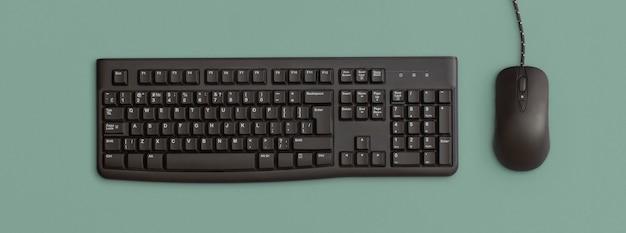 Компьютерная черная клавиатура и мышь на зеленом фоне