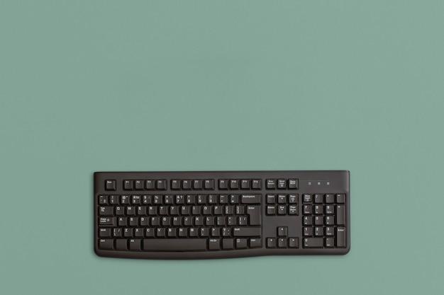 緑の背景にコンピュータの黒いキーボード