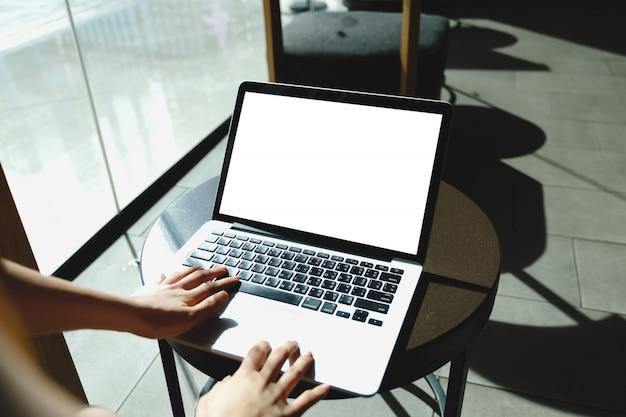 コンピューターの空白の画面とオフィスで机の上のラップトップを使用してテキストを入力する手。